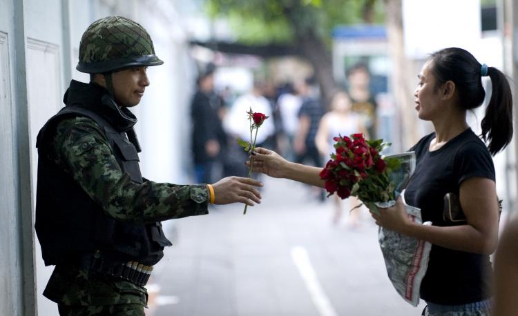 A Bangkok resident hands a soldier a rose in appreciation as he stands guard on Convent Road in Bangkok on April 30. Soldiers and police are deployed throughout the city.(Andy Nelson/Getty Images)