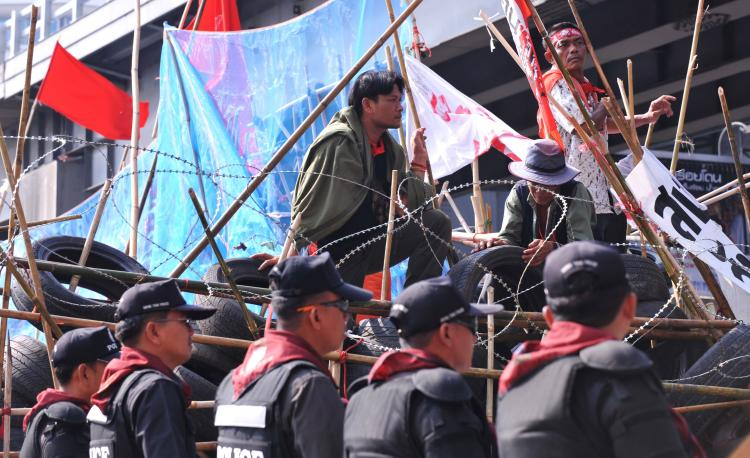 Thai anti-riot police mount guard next to Thai red shirt anti-government protesters from their fortified camp in the financial central district of downtown Bangkok on May 2. (Hong Dinh Nam/Getty Images)