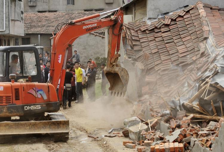 Chinese authorities carry sticks as they stand guard while workers demolish houses which are claimed illegal by the local government in Wuhan, central China's Hubei province on May 7, 2010. (AFP/Getty Images)