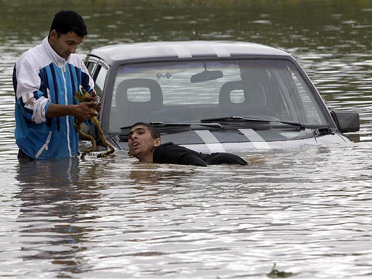 Residents try to salvage their car in the flood water of Vadasz stream near Alsovadasz village on May 17 as heavy rainfall and floods hit Hungary on the weekend. (Attila Kisbenedek/AFP/Getty Images)