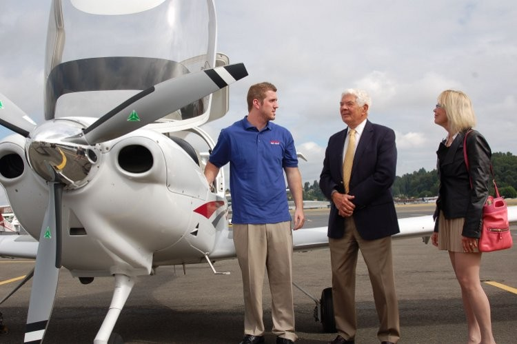 LANDING DOWN: Aviation High School donors James and Sherry Raisbeck welcome pilot and AHS inaugural class graduate Joey Marco after Marco arrived at the groundbreaking in a plane, which he piloted.  (The Keller Group)