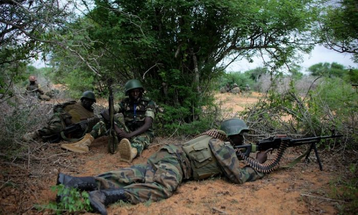 In this handout photograph released by the African Union-United Nations Support Team, soldiers take up a defensive position during a firefight on May 22, operation to seize and liberate territory from the Al-Qaeda-affiliated extremist group Al Shabaab. (Stuart Price/AFP/GettyImages)