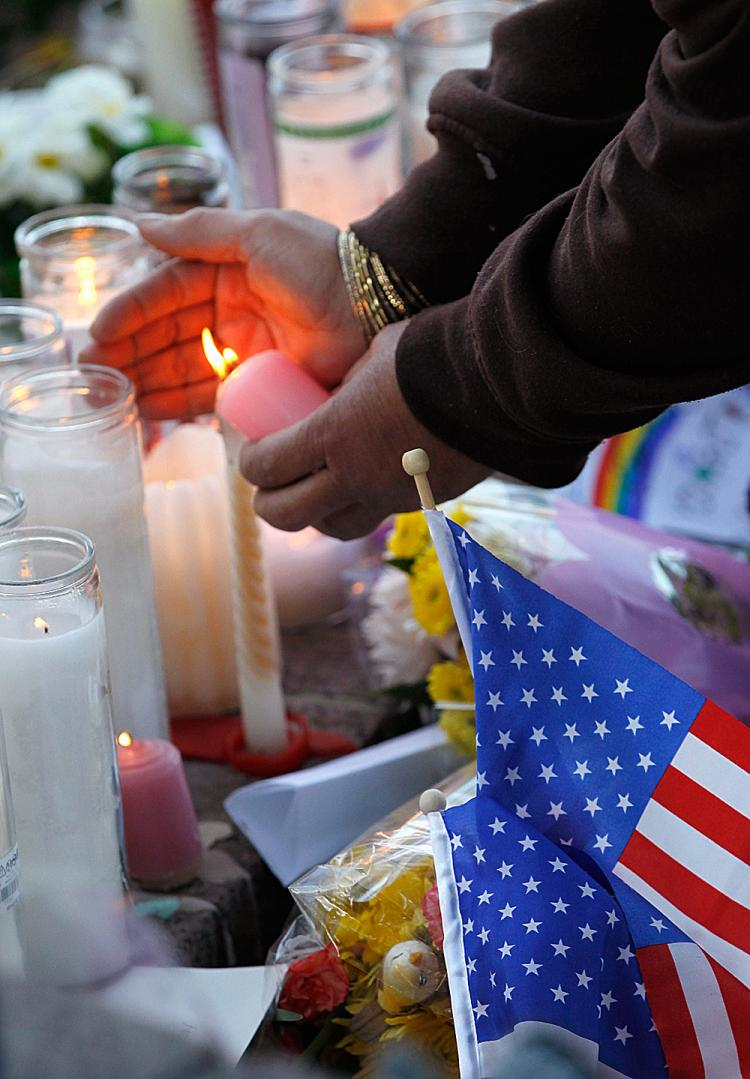REMEMBERED: A woman lights a candle at a makeshift memorial near the district office of U.S. Rep. Gabrielle Giffords (D-Ariz.), a day after a gunman allegedly opened fire during a public event titled Congress on your Corner outside a grocery store in Tucson, Ariz. (Kevin C. Cox/Getty Images)