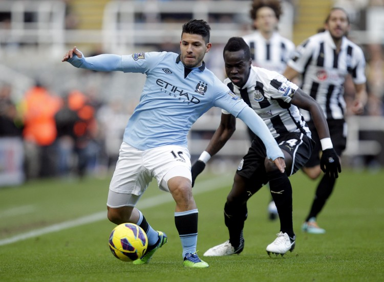 Manchester City's Sergio Aguero fends of Newcastle's Cheik Tiote in English Premier League action on Saturday, Dec. 15, 2012. (Graham Stuart/AFP/Getty Images)