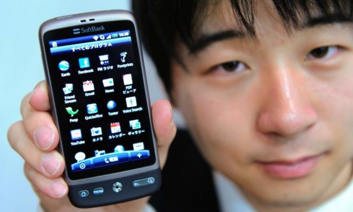 An Asian man holding a smartphone in Tokyo on March 28. (Toru Yamanaka/AFP/Getty Images)