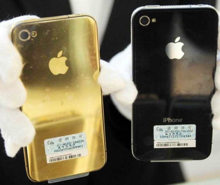 A shopkeeper shows golden accessories of Iphone at a shopping mall on March 25, 2011 in Qingdao, China.  (ChinaFotoPress/Getty Images)