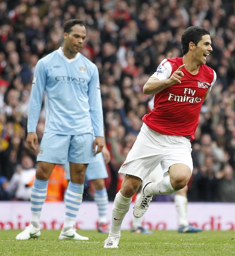 Arsenal's Mikel Arteta celebrates his winning goal as Manchester City's Joleon Lescott looks on glumly. (Ian Kington/AFP/Getty Images)