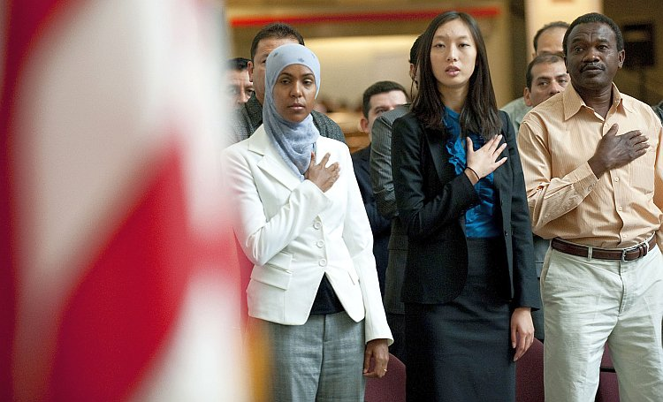 An Asian woman is among a group of newly naturalized U.S. citizens