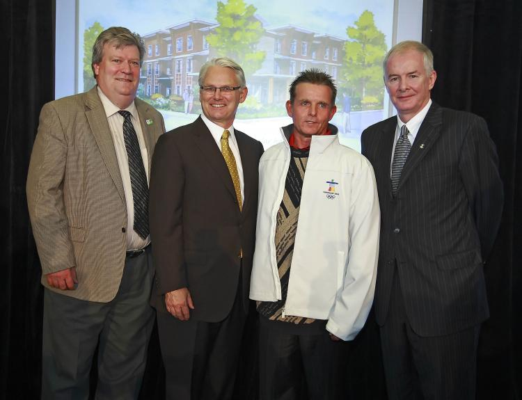 VANOC and the Province of B.C. plan to convert Olympic modular units into affordable homes after the Games. (L-R) Housing Minister Rich Coleman, Premier Gordon Campbell, Mark from Phoenix Drug and Alcohol Centre, and VANOC CEO John Furlong.  (B.C. Housing)