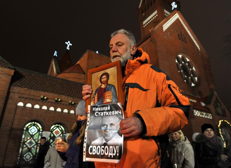 A man holds an icon and a poster depicting Mikola Statkevich, a presidential candidate, who was jailed after last month's controversial vote, reading 'Free Statkevich!' in Minsk, on Jan. 19, marking one month after the election. Following the Dec. 19, 2 (Viktor Drachev/AFP/Getty Images)