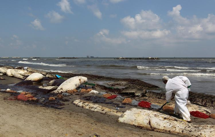 A BP cleanup crew removes oil from a beach on May 23, at Port Fourchon, Louisiana. Officials now say that it may be impossible to clean the hundreds of miles of coastal wetlands affected by the massive oil spill which continues gushing in the Gulf of Mexico. (John Moore/Getty Images)