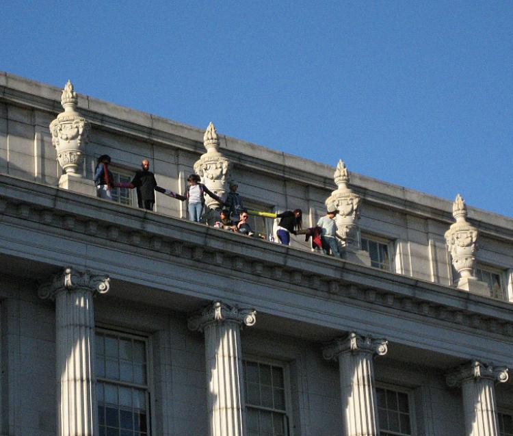 Several University of California, Berkeley students stand on the ledge of a four-story campus building to protest education cuts on Thursday, March 3 in Berkeley, Calif. (Vicky Jiang/The Epoch Times)