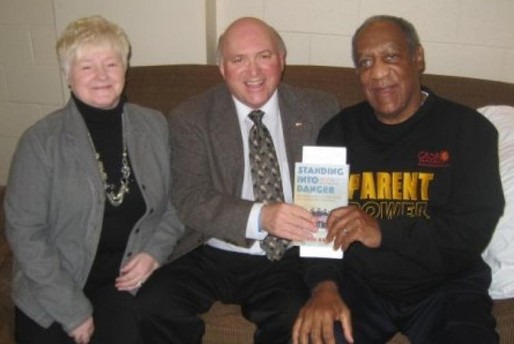 Bill Cosby invited St. Lawrence Mayor Wayde Rowsell and his wife, Carmelita, to attend his show in St. John's, Newfoundland and Labrador (NL), on Dec. 4, 2009, and also to meet him backstage prior to the show. The men are holding 'Standing into Danger,' a book by Cassie Brown about the U.S. naval disaster off the coast of NL in WWII and the dramatic rescue by the people of the nearby towns of St. Lawrence and Lawn. (Courtesy of Wayde Rowsell)