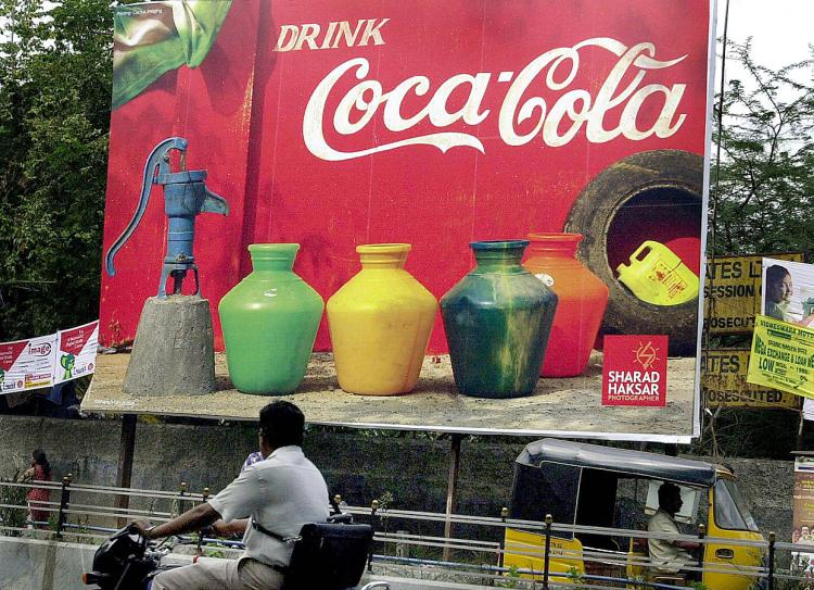 DRINK UP, PAY UP: Commuters pass a Coca-Cola billboard in Chennai, India. A new tax proposal by President Barack Obama would force multinational companies to pay higher taxes on overseas profits.  (AFP/Getty Images)