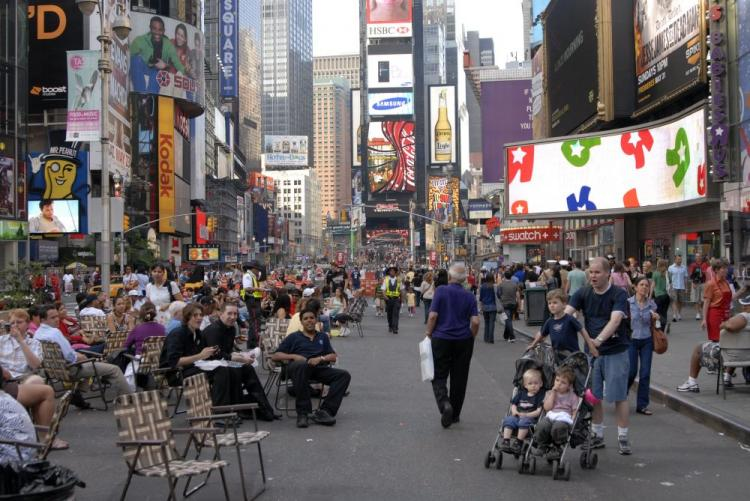 People sit on lawn chairs on what used to be one of New York's busiest streets in Times Square. Parts of Broadway were officially closed to vehicle traffic on the night of May 24. (Joshua Philipp/The Epoch Times)