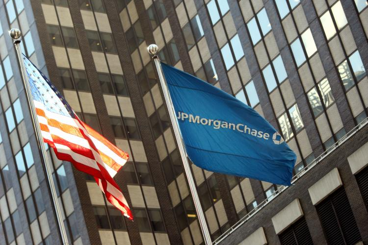 The JP Morgan Chase flag flies near its headquarters in New York. Chase announced that it would modify loan terms and temporarily freeze foreclosures. (DON EMMERT/AFP/Getty Images)