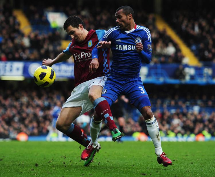 Aston Villa's Stuart Downing and Ashley Cole vie for the ball at Stamford Bridge on Sunday. (Jamie McDonald/Getty Images)