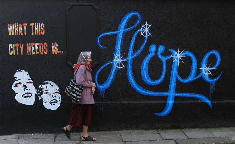HOPE: In a file picture taken on November 25th, 2011, a woman walks past a wall covered in graffiti, which reads 'What This City Needs Is Hope' on a building in Dublin, Ireland.