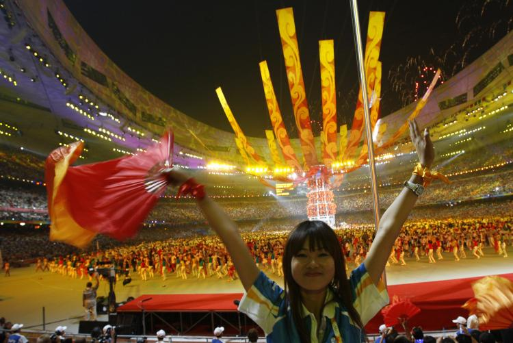 An audience member cheers during the closing ceremony of the Beijing Olympics. (Adrian Dennis/AFP/Getty Images)