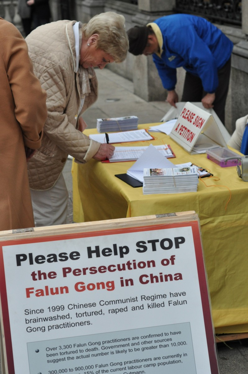 Woman signing a petition to call on Taoiseach (Prime Minister) Enda Kenny to urge China to end the persecution of Falun Gong (Martin Murphy/The Epoch Times)