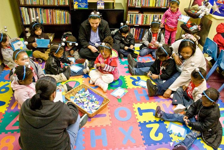 Health care workers play with and teach homeless children in the Floating Hospital, a medical clinic in Long Island City.  (The Epoch Times)