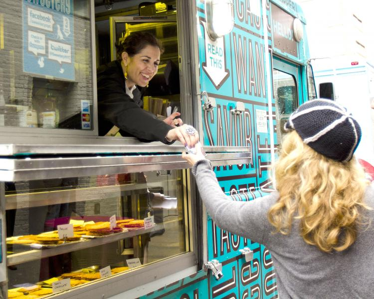 MACAROON HAND-OFF: Samira, co-owner of Sweetery, gives a coconut macaroon to Carly Caryn on Monday at the Food Truck Rally in West Chelsea on 21st and 22nd Streets between Tenth and Eleventh Avenues. (Phoebe Zheng/The Epoch Times )