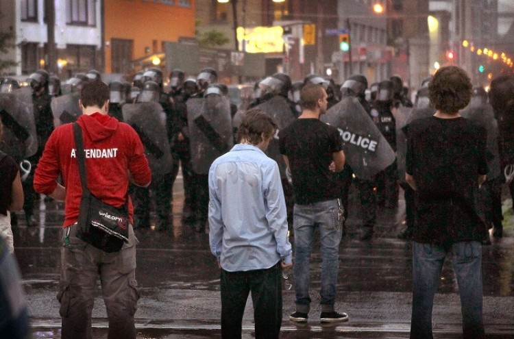 Police officers hold back demonstrators at the G20 summit in Toronto. Critics say that many questions still remain unanswered after the Toronto Police Service released the G20 After Action Review last week. (Scott Olson/Getty Images)