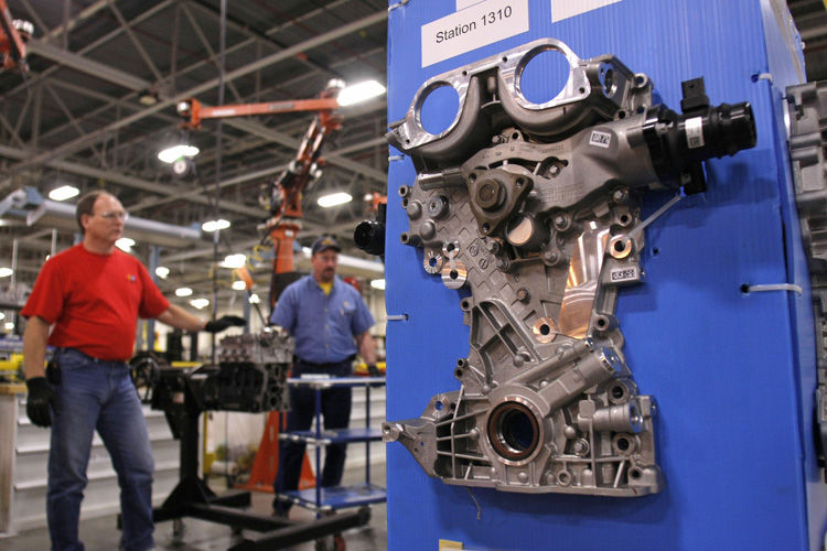 An engine part is displayed as GM workers demonstrate an assembly process