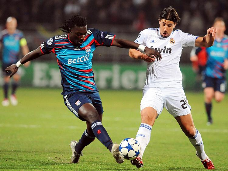 CHAMPIONS LEAGUE: Lyon's Bafetimbi Gomis and Real Madrid's Sami Khedira challenge for the ball in Tuesday's action. (Philippe Merle/AFP/Getty Images)
