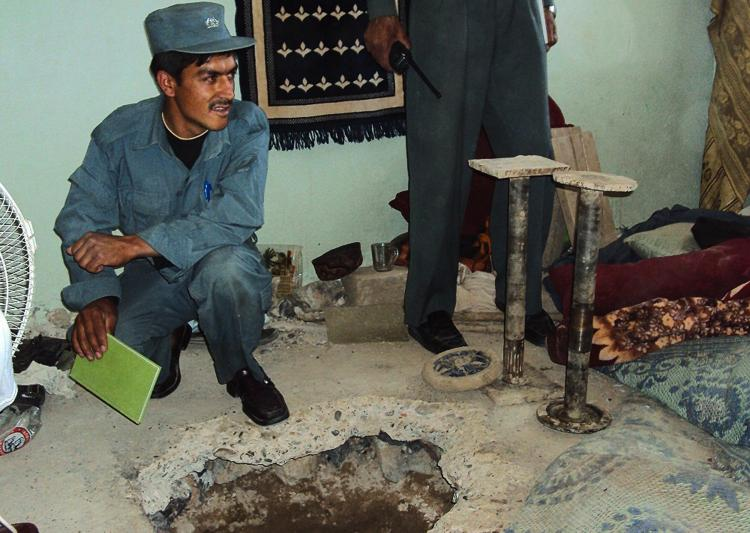 BAD BREAK: An Afghan policeman sits next to the entrance of the tunnel in room number 7 of the Political Prisoners section through which Taliban fighters escaped in an audacious jailbreak in Kandahar city on April 25. The government admitted it was a security disaster in the prison, the second largest break in three years. (STR/Getty Images)