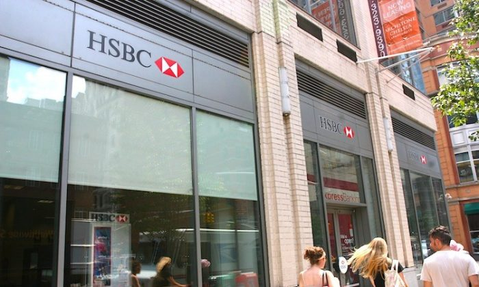 Young people walk past an HSBC bank in midtown Manhattan, New York, on Aug. 1. The banking giant is looking to shed retail bank branches in New York to focus more on investment and corporate banking. (Jaya Gibson/The Epoch Times)