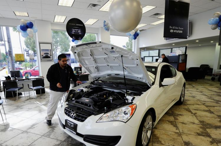 SELLING FAST: Workers move a 2011 Hyundai Genesis Coupe for display in the showroom at a Hyundai dealership in Glendale, Calif. (Kevork Djansezian/Getty Images)