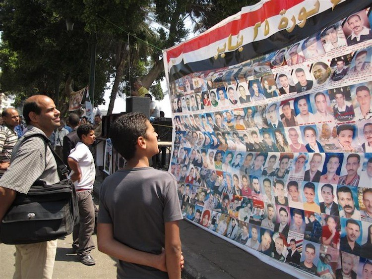 People look at the photos of those killed on Jan. 25. The banner was displayed next to the television building in Cairo, Egypt. The image is part of an exhibit and book that document this year's events in Egypt and Israel. (Yaira Yasmin/The Epoch Times)