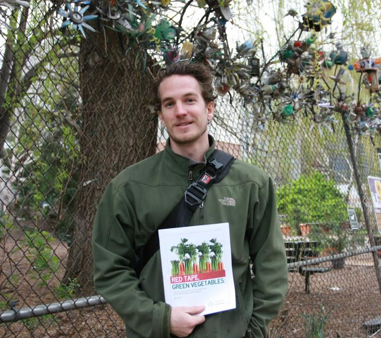 A TOUGH SELL: Travis Tench, who is involved in community-run farmers markets, stands in front of a community garden on the Lower East Side to talk about the difficulties faced by low-income community groups that want to start a market of their own. He holds up a report released by Borough President Scott Stringer on the matter. (Tara MacIsaac/The Epoch Times)