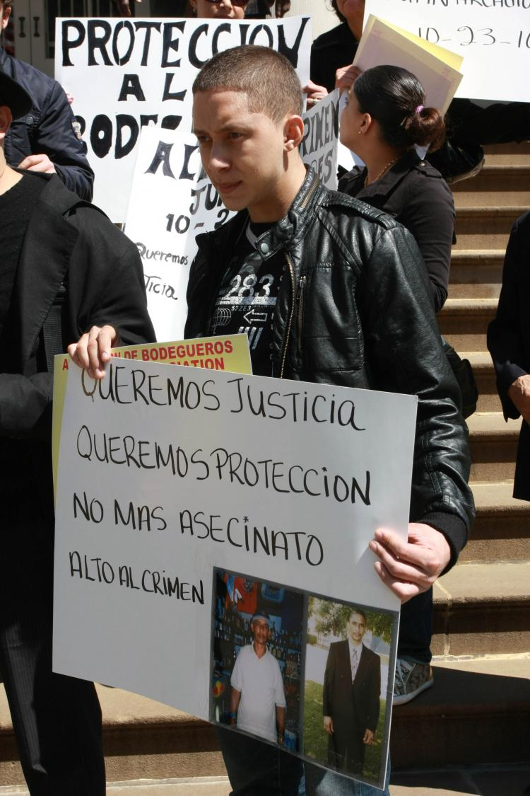 LOST TO VIOLENCE: The son of Juan Torres, who was shot in his bodega in October 2010, holds up photos of his father and calls for increased safety in the city's bodegas on Thursday at City Hall.  (Tara MacIsaac/The Epoch Times)