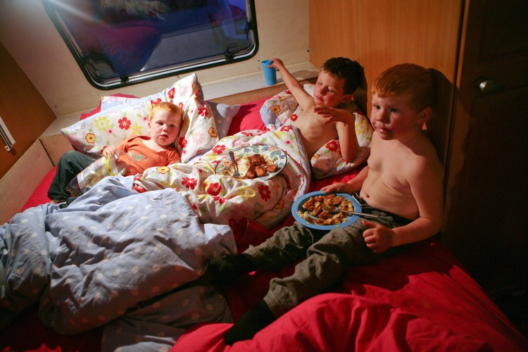 NOT LEAVING: Three children in a trailer at Dale Farm Travellers Site in Essex have dinner before being put to bed, despite a court order to leave the site by midnight wednesday. (Courtesy of Mary Turner)