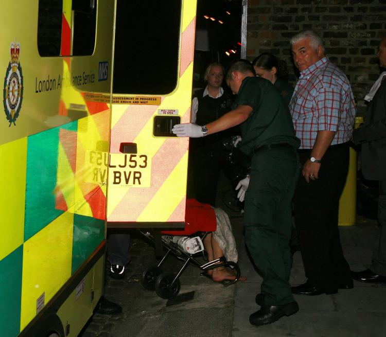 Amy Winehouse is escorted out of home in a wheelchair by paramedics after a 999 call made by her father, Mitch Winehouse. (ISOIMAGES.COM)