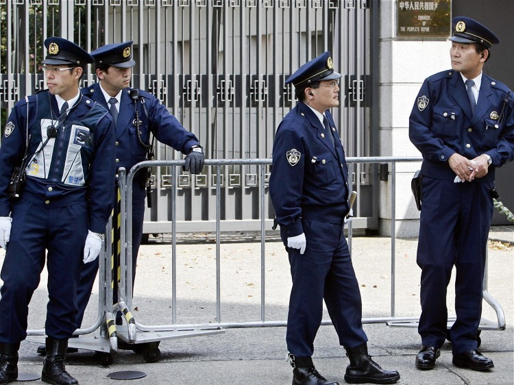 Policemen stand guard in front of the Chinese Embassy in Tokyo