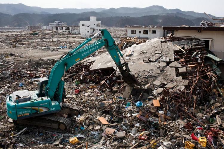 Japanese workers use a hydraulic machine to demolish a wrecked building in the tsunami-devastated town of Rikuzentakata, Iwate prefecture, on April 2, 2011. (Yasuyoshi Chiba/AFP/Getty Images)