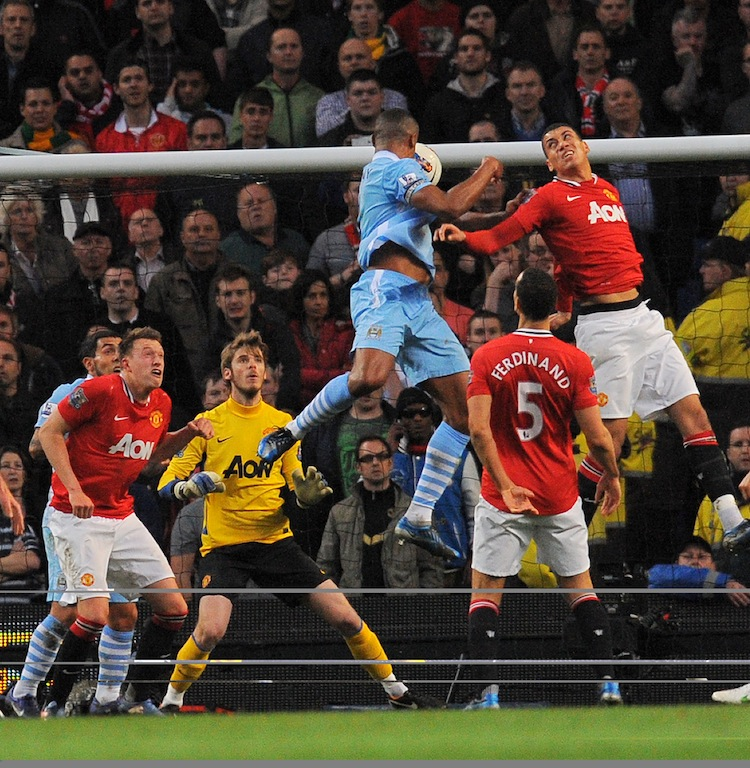 Vincent Kompany rises above the Manchester United defenders to put Manchester City ahead. (Andrew Yates/AFP/Getty Images)