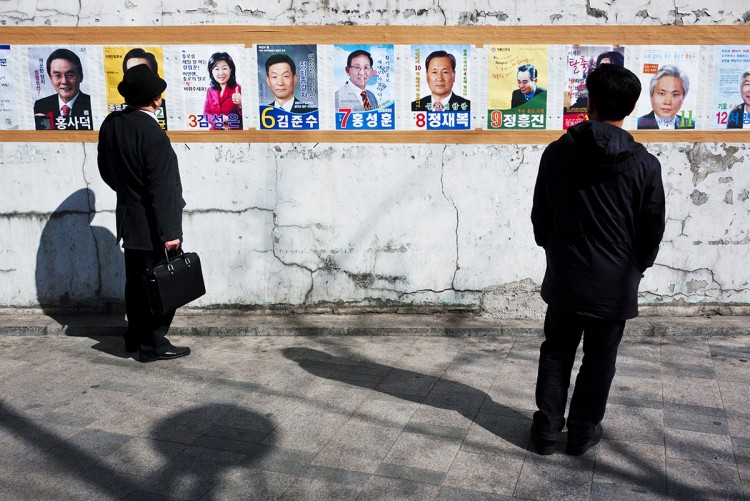 South Korean voters view election posters on April 11.