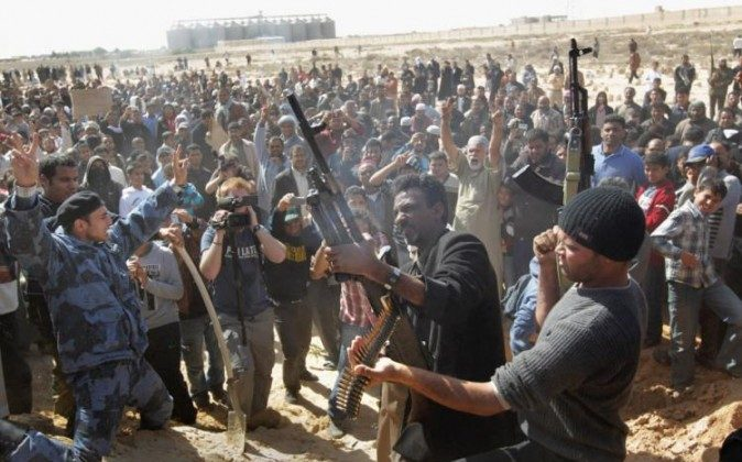 Rebel fighters shoot into the air during a funeral for slain comrades on March 3, in Ajdabiya, Libya. (John Moore/Getty Images)