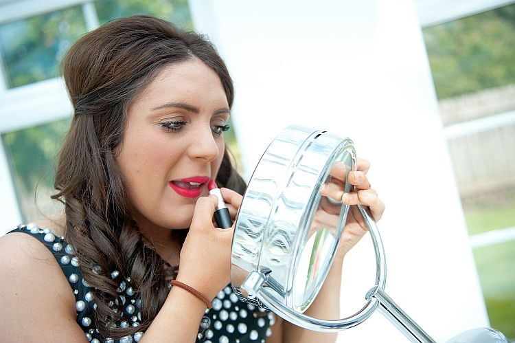 A young woman applies lipstick