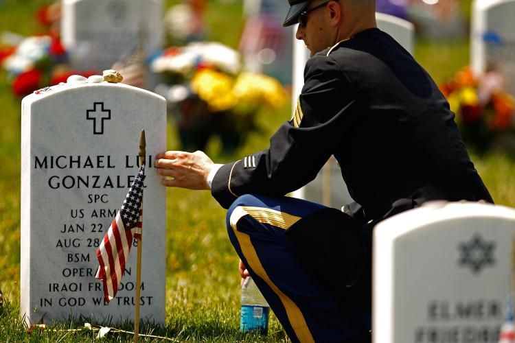 US Army Sgt. Brian Scott touches the grave marker of his friend and gunner Army Specialist Michael Luis Gonzales on Memorial Day May 31, in Arlington, Virginia. Today many Americans will pay tribute to relatives and friends who lost their lives in battles. (Chip Somodevilla/Getty Images)