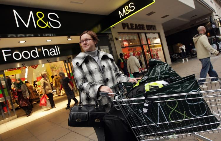 HIGH STYLE: In this file photo, a woman stands with her shopping cart full of M&S shopping bags outside the Marks and Spencer department store on Oxford Street, London. The High Street shop plans to return to Paris in a store opening on the Champs Elysees. (Oli Scarff/Getty Images )