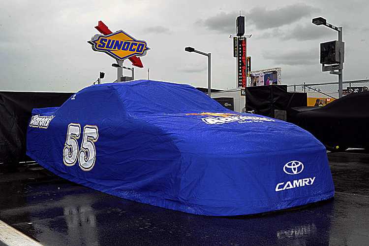 The #55 Aaron's Toyota of Mark Martin sits covered on the grid Sunday. The rain has remained in central Florida, pushing back the start time of the Daytona 500 until 7 p.m. Monday. (John Harrelson/Getty Images for NASCAR)