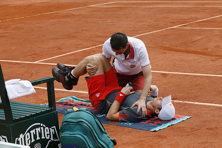 Andy Murray's trainer tries to unkink the fourth-ranked player's spasming lower back during his second-round French Open match against Finland's Jarkko Nieminen. (Patrick Kovarik/AFP/GettyImages)