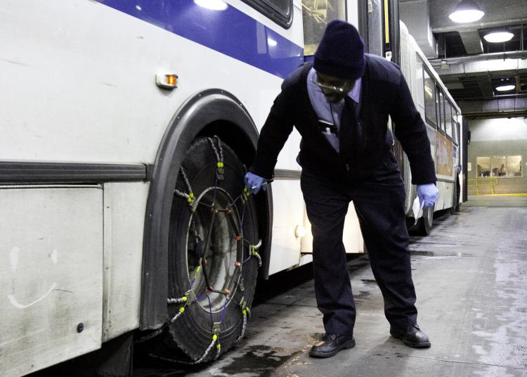 FINAL CHECK: MTA Bus driver David Kemp does a final check of his bus before it hits the road Tuesday. Up to 12 inches of snow have been predicted.  (Phoebe Zheng/The Epoch Times)