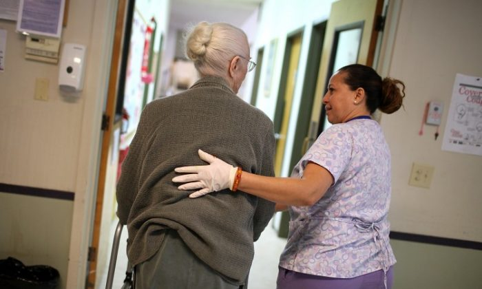 A program assistant at an adult care center helps her elderly patient. Cuts in cost-of-living adjustments impact retirees, making it more of a challenge to pay for health care services. (Justin Sullivan/Getty Images)