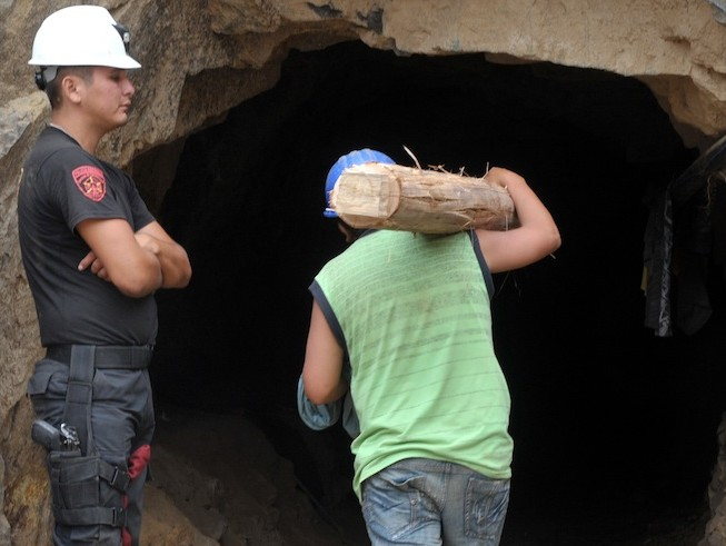 A policeman stands guard as a rescuer carries a timber post into the mine for use as a tunnel support during an operation to rescue nine miners at the Cabeza de Negro copper mine. (Cris Bouroncle/AFP/Getty Images)